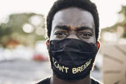 Young black man wearing face mask during equal rights protest - Concept of demonstrators on road for Black Lives Matter and I Can't Breathe campaign - Focus on eyes