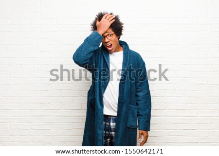 young black man wearing pajamas with gown raising palm to forehead thinking oops, after making a stupid mistake or remembering, feeling dumb against brick wall