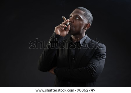Young black man wearing suit gangster style smoking cigar isolated on dark background. Studio portrait.