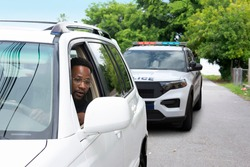 Young black man with a very worried look on his face is looking at the police car that has pulled him over in his rearview mirror reflecting the problems between citizens and some police departments.