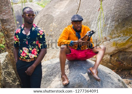 Young black men sitting on a rock listening to a radio
