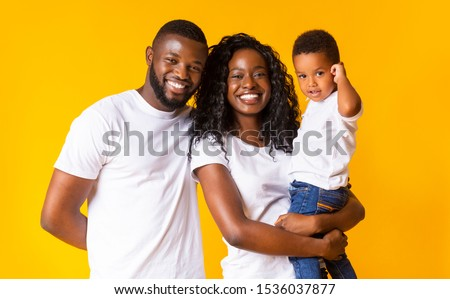 Young black parents with adorable infant son over yellow studio background, free space #1536037877