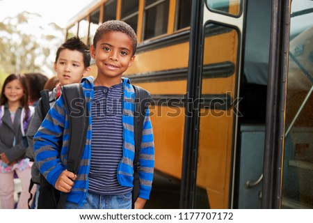Young black schoolboy and friends wait to get on school bus