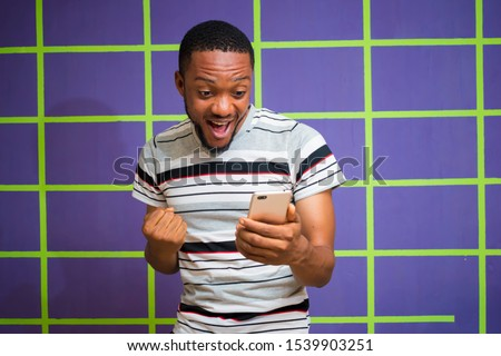 Young black stratified African man celebrating his victory after receiving Good news from his mobile phone. man standing on a colorful wall excited after checking his mobile phone  Foto d'archivio ©
