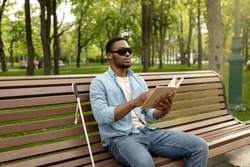 Young black visually impaired man sitting on bench in city park, reading Braille book outdoors. Millennial blind guy in dark glasses studying or enjoying entertainment literature, outside