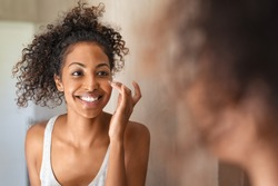 Young black woman applying moisturising cream on cheeck while standing in front of the mirror in bathroom. African american girl applying face cream. Beauty hydrating moisturizer and skincare routine.