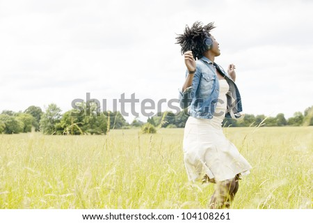 Young black woman dancing in a long grass field while listening to music with her headphones.
