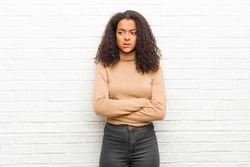 young black woman doubting or thinking, biting lip and feeling insecure and nervous, looking to copy space on the side against brick wall
