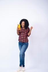 young black woman feeling surprised and happy looking at her phone