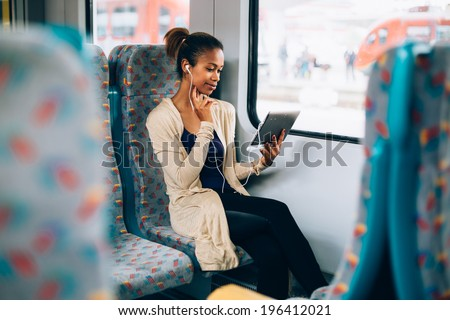 Young black woman listening to music on train using tablet computer