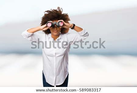 young black woman looking through the binoculars #589083317