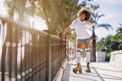 Young black woman on roller skates riding near the beach.