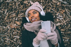 Young black woman on the mobile phone lying on peaces of wood near the royal palace in Madrid during winter