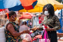 Young black woman paying money to a vendor for a purchased item in the market. Two women wearing locally made mask and surgical mask on the street in covid-19 pandemic season for protection.
