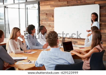 Young black woman presenting to colleagues from whiteboard #629123999