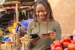 young black woman selling in a local african market using her mobile phone and credit card to do a transaction online smiling
