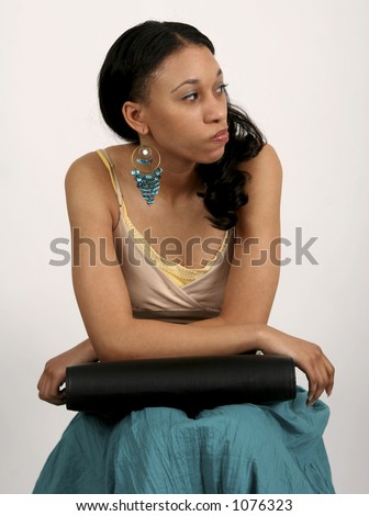 Young black woman sitting impatiently with portfolio in her lap