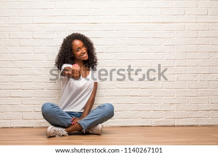 Young black woman sitting on a wooden floor inviting to come, confident and smiling making a gesture with hand, being positive and friendly Сток-фото ©