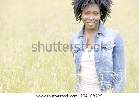 Young black woman standing in a yellow field, smiling.