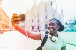 Young black woman taking selfie with smart phone hand hold with Milan cathedral in background, smiling - happiness, traveler, technology concept
