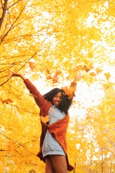 Young black woman throwing autumn leaves in the autumn forest