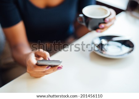 Young black woman using phone in coffee shop
