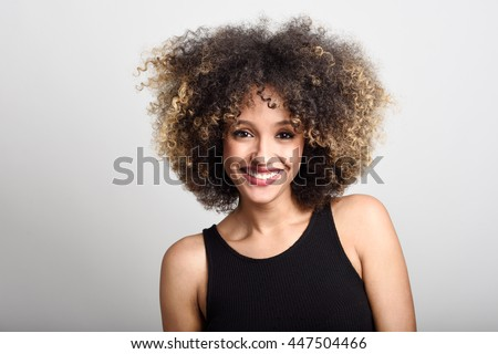 Young black woman with afro hairstyle smiling. Girl wearing black dress. Studio shot. #447504466