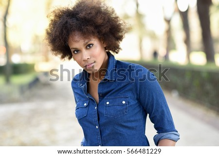 Young black woman with afro hairstyle standing in urban background. Mixed woman wearing blue shirt and shorts.