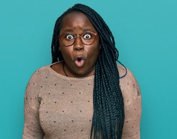 Young black woman with braids wearing casual clothes and glasses scared and amazed with open mouth for surprise, disbelief face