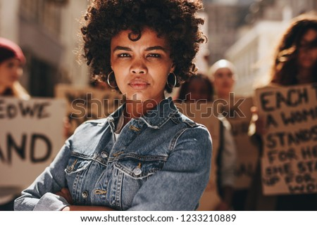 Young black woman with group of demonstrator in background outdoors. African woman protesting with group of activists outdoors on road.