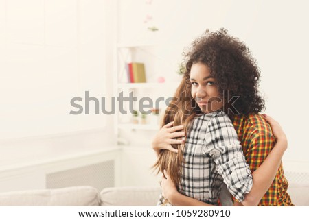 Young black woman with sly facial expression embracing friend, insincere female hiding her envy or jealous, thinking about deception. Distrust between friends, copy space