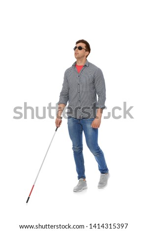 Young blind person with long cane walking on white background #1414315397