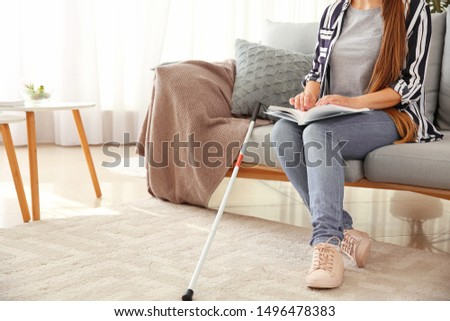 Young blind woman reading book written in Braille at home Foto stock ©