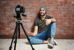 Young blogger with recording video against brick wall background