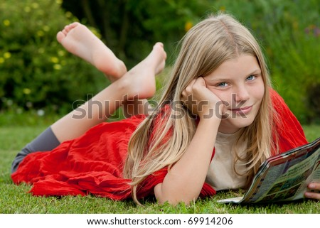 Young blond blue-eyed teenage girl lying on the grass on the garden and reading a teen magazine.