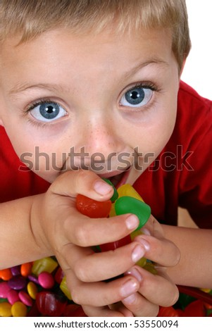 Young blond boy eating a hand full of candy