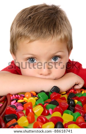 Young blond boy in front of a table filled with sweets