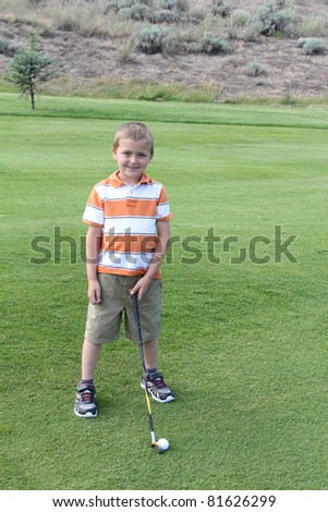 Young blond boy standing in the fairway before his shot