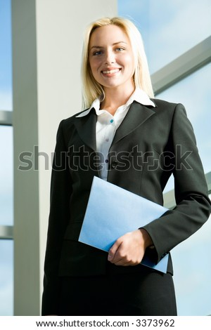 Young blond business woman in black suit holding the blue case in her hand standing in the building with glassy walls
