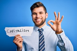 Young blond businessman with beard and blue eyes holding paper with capitalism message doing ok sign with fingers, excellent symbol