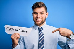 Young blond businessman with beard and blue eyes holding paper with capitalism message with surprise face pointing finger to himself