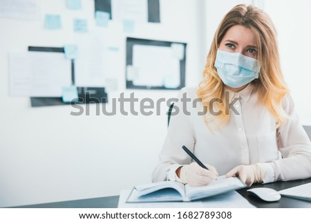 young blond businesswoman manager in medical protection mask and gloves takes notes to her planner working in office during Covid-19 epidemy, virology concept