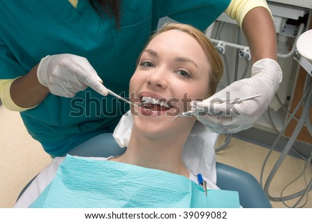 Young blond Caucasian female opening her mouth while African-American ethnic dentist in white latex gloves check condition of her teeth