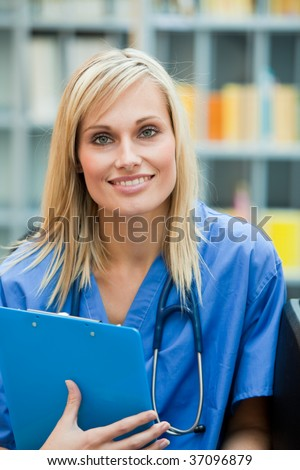 Young blond doctor at work in hospital smiling at the camera