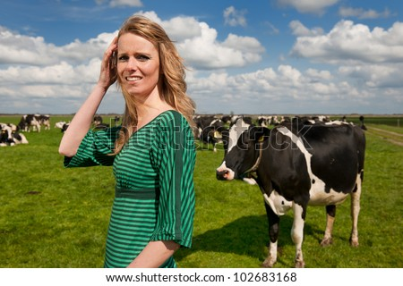 Young blond Dutch girl in farm field with black and white cows
