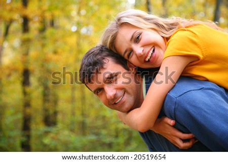 Young blond embraces man from back
