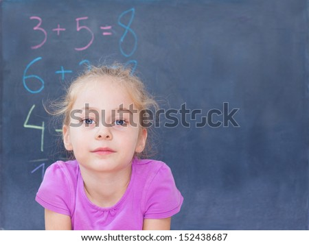 Young blond five years old caucasian girl in front of blackboard at school - mathematics lesson