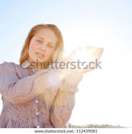 Young blond girl holding the sun in her hands, with sunrays filtering through, against a blue sky.