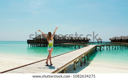 Young blond girl in a colored dress near water bungalows located in a small island of Maldives. #1082634275