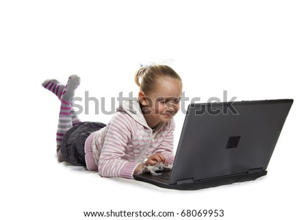 Young blond girl playing with laptop isolated over white